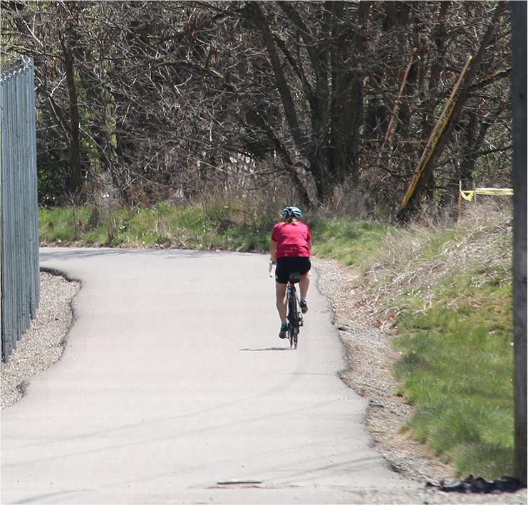 Bicyclist riding down a wooded trail